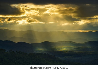 Yellow sun shafts through cloudy sky with long mountain range  and brighten foreest in Tak, Thailand