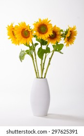 Yellow sunflowers in a vase on a white background.