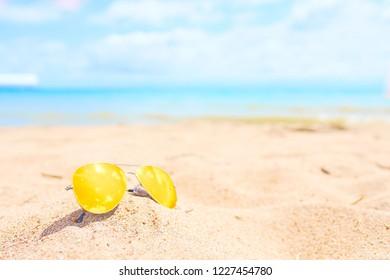 Yellow sunglasses on the beach. Resort concept