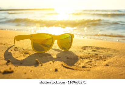 Yellow sunglasses on yellow sand beach with blue sea and sky background summer