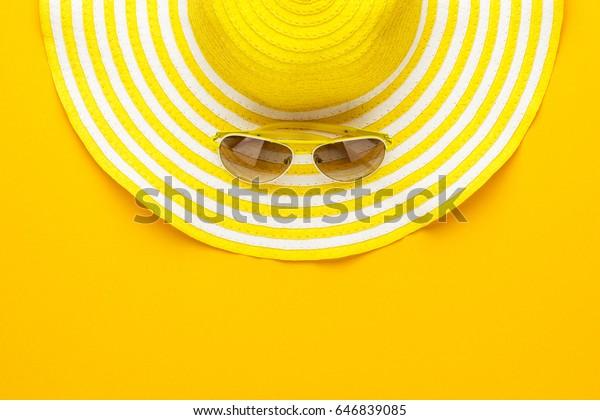 黄色いサングラスと縞模様のレトロな帽子。夏のコンセプト