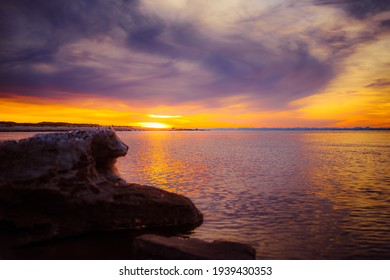yellow sunset in the Baltic Sea where the river flows into the sea, there are low blue clouds in the sky