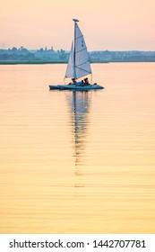 Yellow sunset on the water with a sailing catamaran. Volga, Tver region