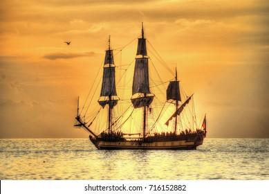Yellow sunset and sailing ship.