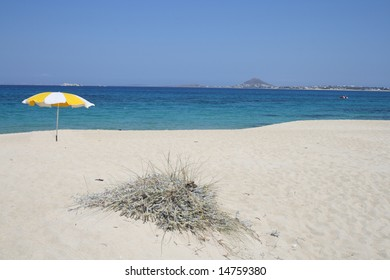 Yellow sunshade on the white greek beach of Mikri Vigla, Naxos, Greece