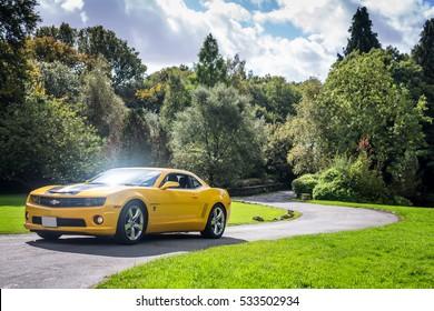 Yellow supercar Chevrolet Camaro driving through English countryside in Bolton Lancashire 2013