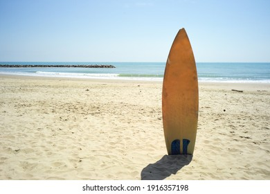 Yellow surfboard in the sand beach with horizontal line of seascape in background