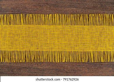 Yellow Table Runners with Fringe on brown wooden table rustic background, copy space.  Decorative Border Fabric Background. Easter decorative textile background