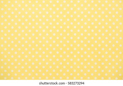 Yellow tablecloth with white dots background texture.