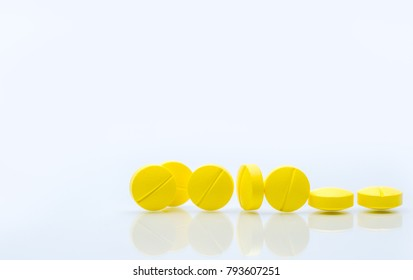 Yellow tablets pills isolated on white background with copy space. Pile of medicine.
