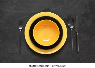 Yellow tableware on black wood table. Top view point, flat lay.