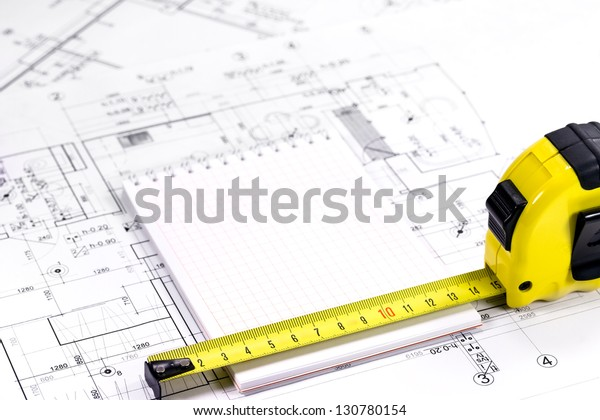 Yellow tape measure on architectural drawing