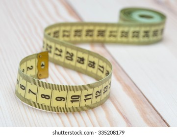 Yellow tape measure on wooden background