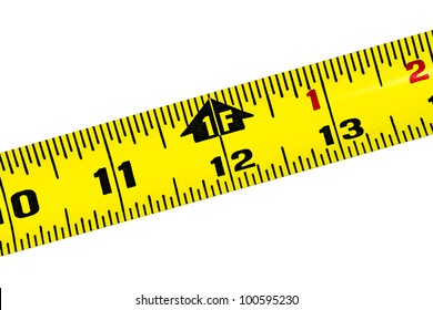 Yellow tape measure rule at the 1 foot mark diagonally placed on pure white background
