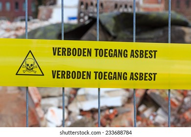 Yellow tape on fence with Dutch text 'no entry asbestos' in front of demolition site