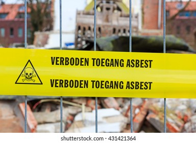Yellow tape on fence with Dutch text 'no trespassing asbestos' in front of demolition site
