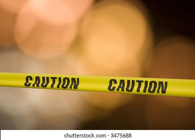 Yellow tape with the word caution on it across a warning light background