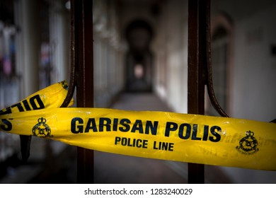 Yellow tape with wordings of police line do not cross in both English and Malay language