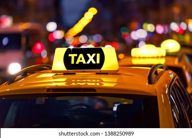 Yellow taxi cab and blurred city lights background at night with colorful bokeh