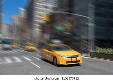 Yellow taxi cab driving quickly down the street in New York City with motion blur background