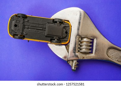 yellow taxi car in iron wrench isolated on blue background. bottom of car.