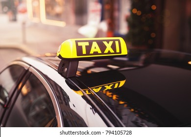 yellow taxi car roof sign at night. taxi car on the street at night. selective focused image.