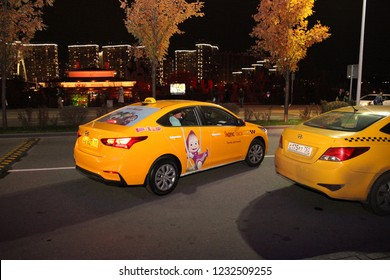 """Yellow taxi car with a sticker from the cartoon """"Masha and the Bear"""", Yandex taxi company near the shopping center. Moscow. 26.10.2018"""