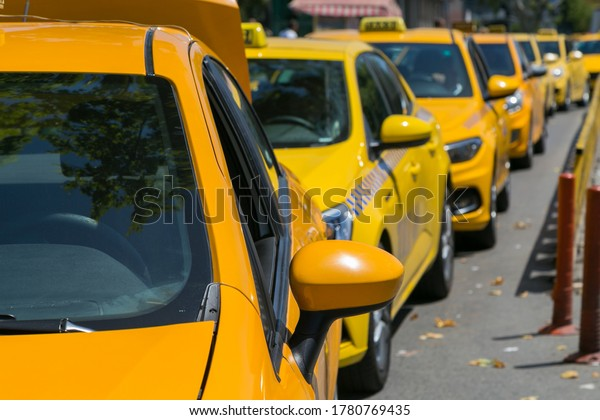Yellow taxi cars on the empty street, taxi cab parking lot with yellow cars standing, set of taxicabs in the streets, taxis