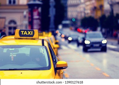 yellow taxi cars in row and blurred city traffic detail - european cityscape