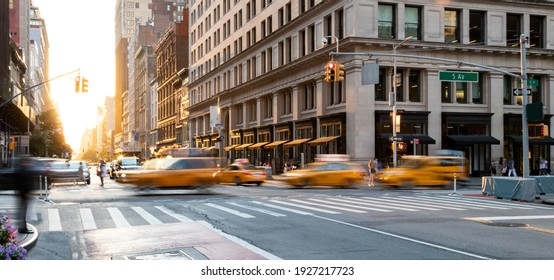 Yellow taxis driving through the busy intersection of 5th Avenue and 23rd Street in Manhattan, New York City USA