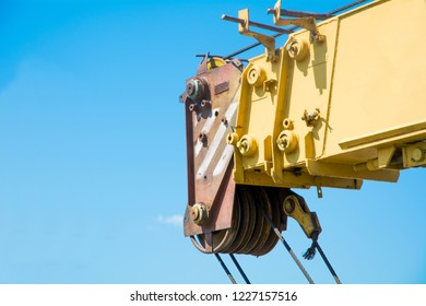 Yellow telescopic arm of a mobile crane against deep blue sky and white clouds