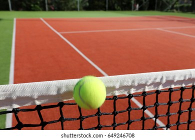 yellow tennis ball hits the net in a matchpoint on a deep orange clay court, close-up