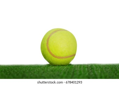 yellow tennis ball hitting the sidelines on green artificial tennis court in writh background.