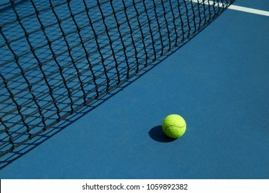 Yellow tennis ball is laying near black opened tennis court's net. Contrast image with satureted colors and shadows. Concept of tennis outfit photografing.