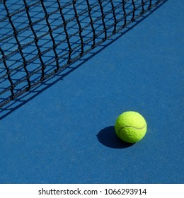 Yellow tennis ball is laying near black opened tennis court's net. Contrast image of sport equipment with satureted colors and shadows. Concept of tennis outfit photografing.