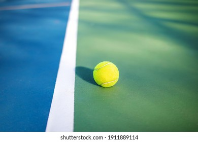 Yellow tennis ball next to sideline in outdoor tennis court, closeup. Defocused and abstract blue and green rubberized ground surface for shock absorption. Tennis sport texture. Selective focus.