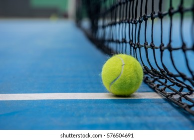 Yellow tennis ball on blue hard court and black net