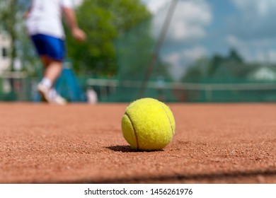 yellow tennis ball on clay court during training session at tennis academy