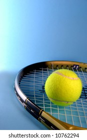 yellow tennis ball and racket over a blue background