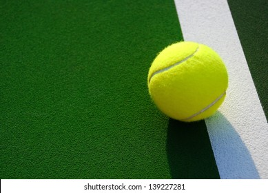 Yellow tennis ball sits just outside of the white line
