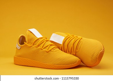 Yellow tennis modern shoes isolated on orange background