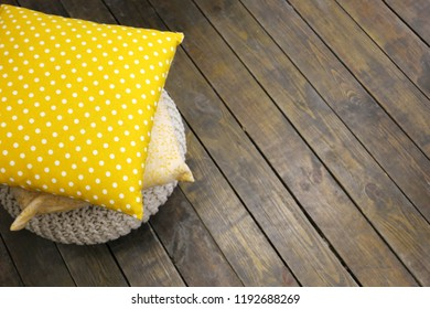 yellow textile pillow with white dots and macrame pillow on the wooden floor on hugge interior