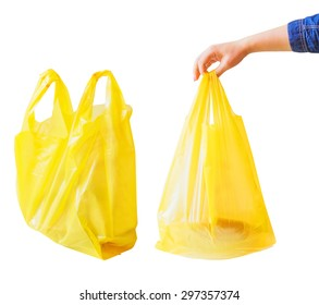 Yellow thin polythene plastic bag isolated on a white background. Woman hand holding a bag with products or goods