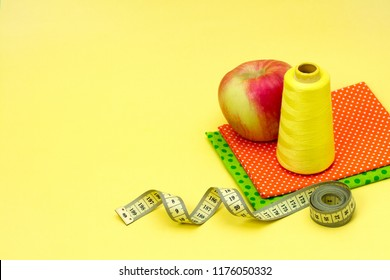 Yellow thread green orange cloth centimeter tape accessories for sewing an apple bright background