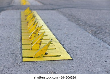 Yellow tire spikes at the entry of a parking lot