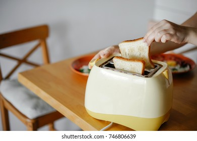 yellow toaster with toasted bread for breakfast inside, on the table in the kitchen interior. Hands Girl pulls out ready toasts.