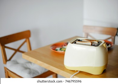 yellow toaster with toasted bread inside on the table in the kitchen interior.