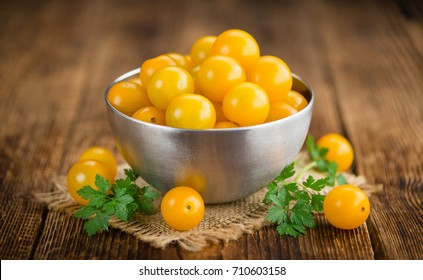 Yellow Tomatoes on an old wooden table as detailed close-up shot; selective focus