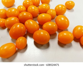 Yellow tomatoes on table background