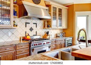 Yellow tones kitchen with tile decorated back-plash, kitchen appliances